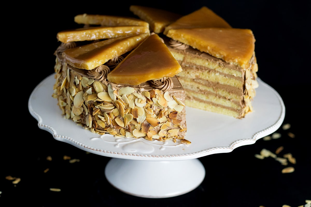 This amazing Hungarian layer cake called Dobos Torte has a fantastic buttery chocolate frosting and crazy caramel topping. Perfect for birthdays! #cake #hungary #chocolate #buttercream   cookingtheglobe.com