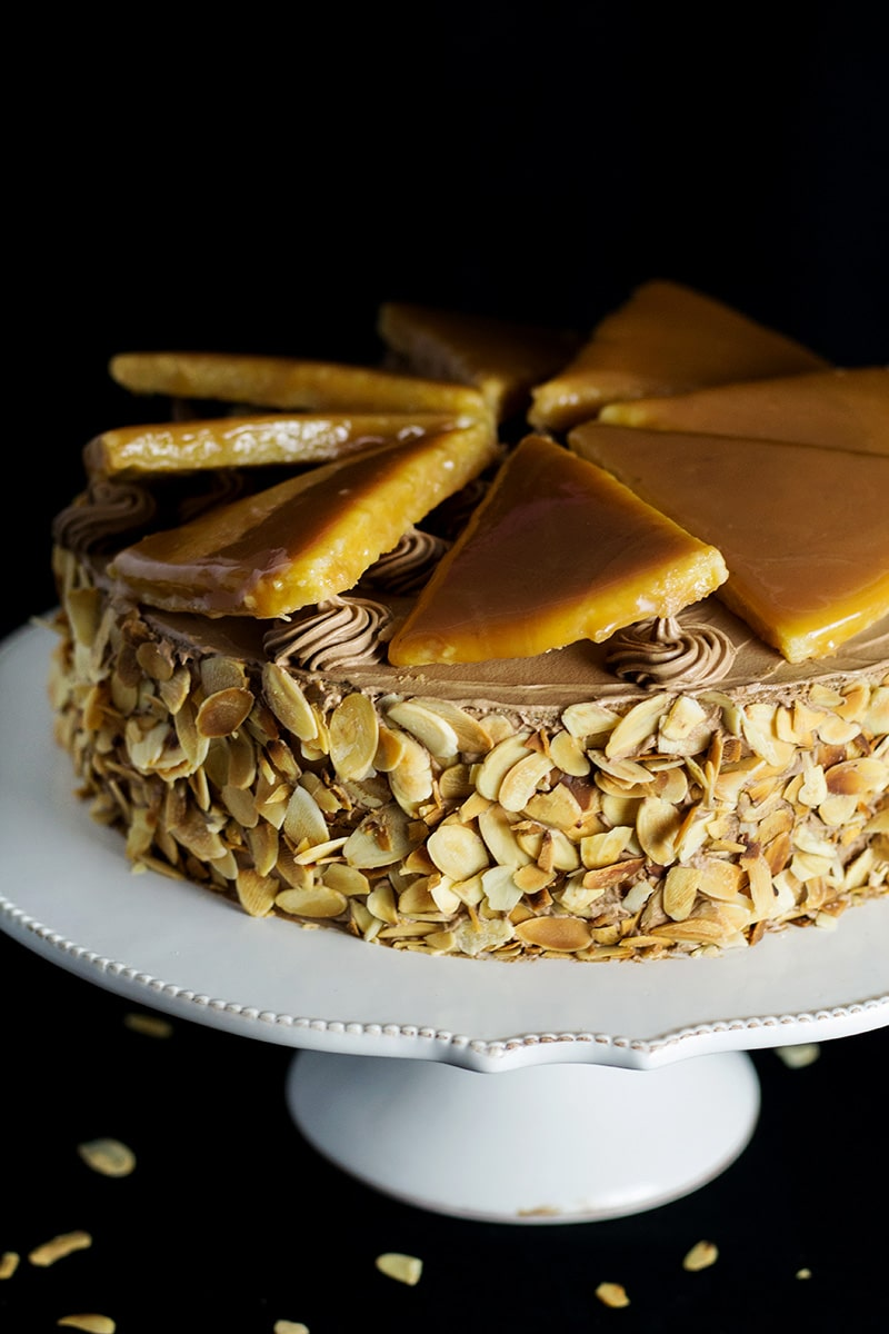 This amazing Hungarian layer cake called Dobos Torte has a fantastic buttery chocolate frosting and crazy caramel topping. Perfect for birthdays! #cake #hungary #chocolate #buttercream | cookingtheglobe.com