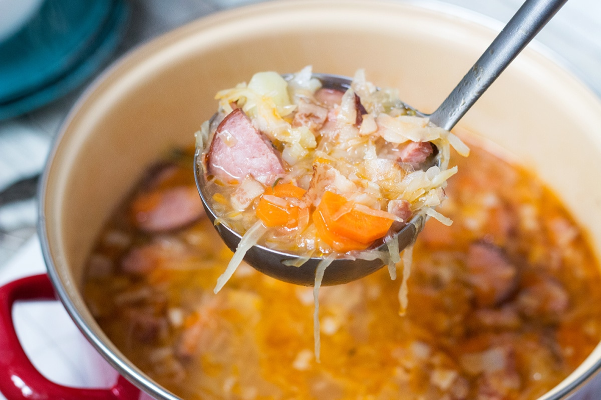 Try this hearty, warming and energizing Polish Sauerkraut Soup with sausage and bacon! | cookingtheglobe.com