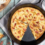Tarte Flambee or Flammkuchen is a savory Alsatian pizza, topped with delicious sauce, onion and bacon!   cookingtheglobe.com