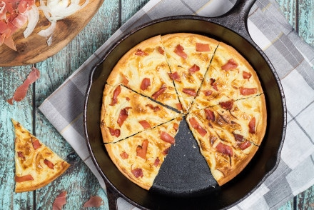 Tarte Flambee or Flammkuchen is a savory Alsatian pizza, topped with delicious sauce, onion and bacon! | cookingtheglobe.com