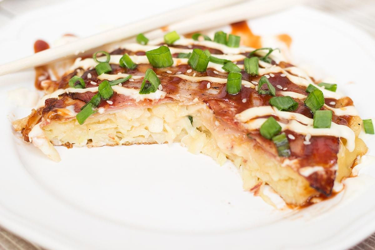 This traditional Japanese pancake (Okonomiyaki) is filled with cabbage ...