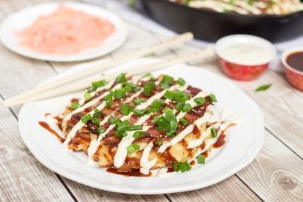 These traditional Japanese pancakes (Okonomiyaki) are filled with cabbage and topped with sliced pork and amazing sauce! | cookingtheglobe.com