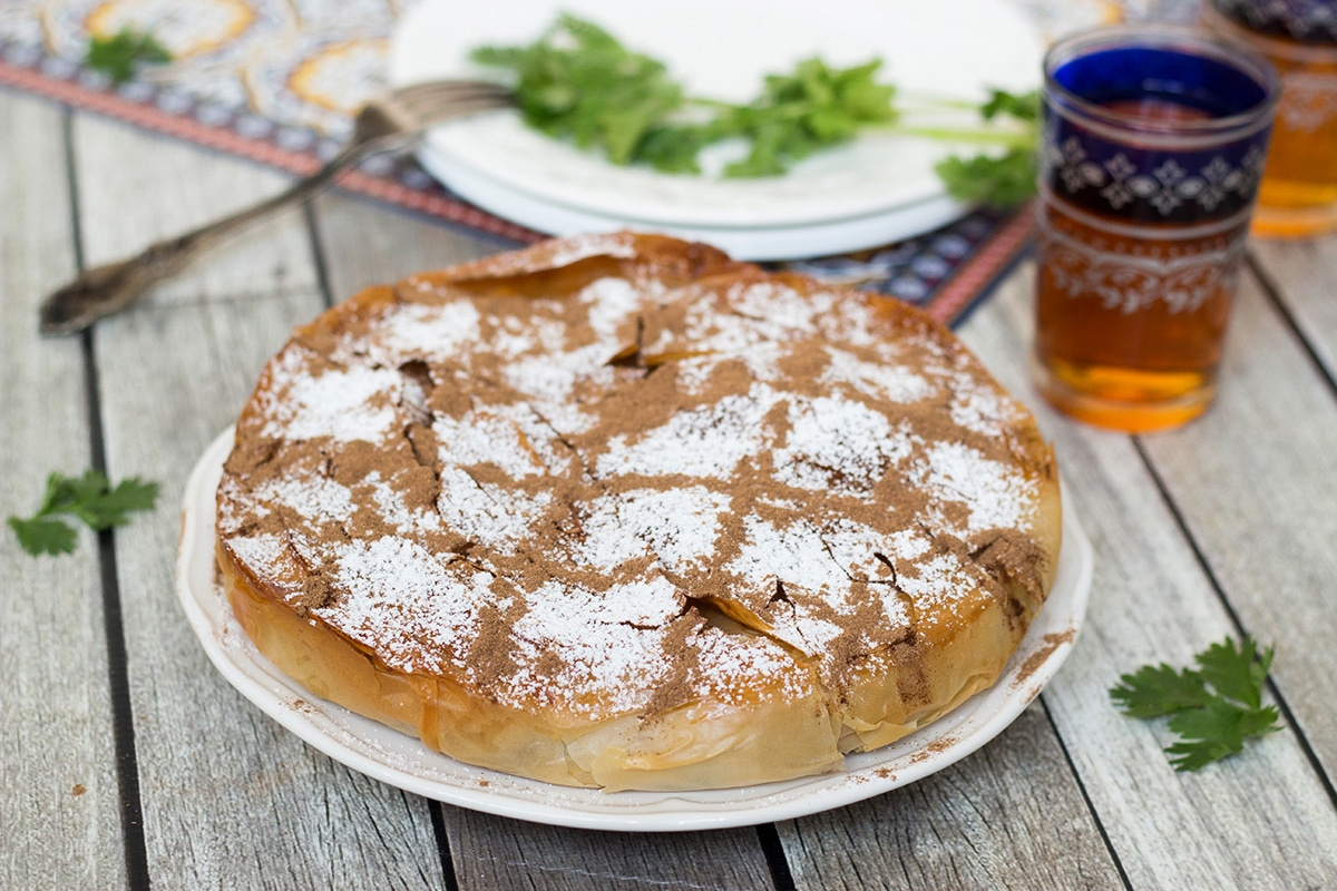 This sweet & savory Moroccan Pie (Pastilla) has a crisp, flaky pastry outside and an amazing cinnamon flavored chicken, onion, and almond filling inside!