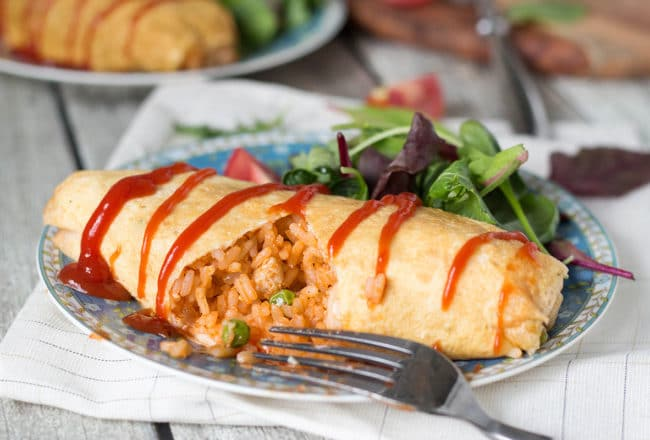 "Omurice is a Japanese dish which got its name from a combo of words ""omelette"" and ""rice"". Basically, it's ketchup flavored rice cooked with chicken, peas, and wrapped in a thin crepe-like omelette. Pure heaven! 