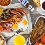 A look at the most iconic morning fare in the world - English breakfast. This hearty meal features eggs, sausages, bacon, beans, mushrooms, and more! | cookingtheglobe.com