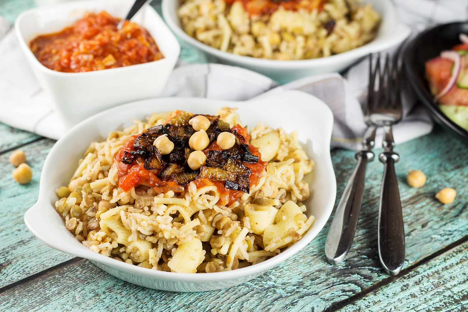 Koshari, or lentils and rice, is a national Egyptian dish. It also features pasta, chickpeas, fried onions, and a homemade tomato sauce. Healthy, filling, nutritious! #vegetarian #vegan  cookingtheglobe.com