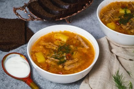 Russian sour cabbage soup served with sour cream and black bread