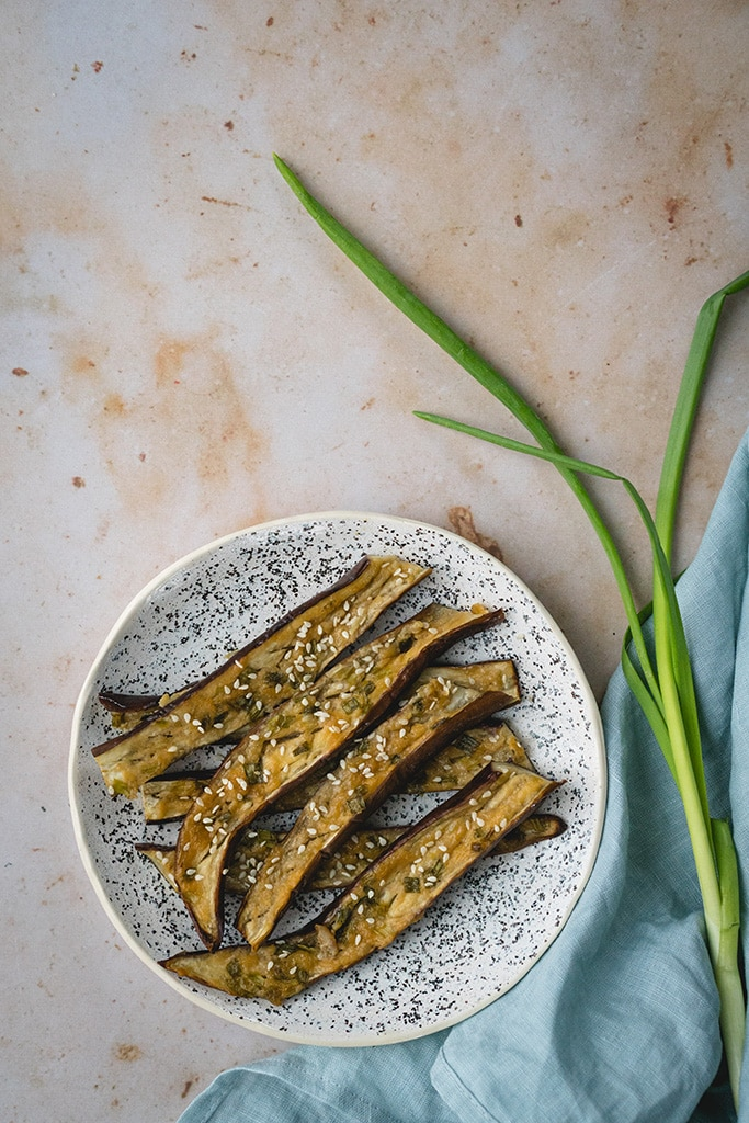 Japanese miso eggplant sprinkled with white sesame seeds and served on a plate