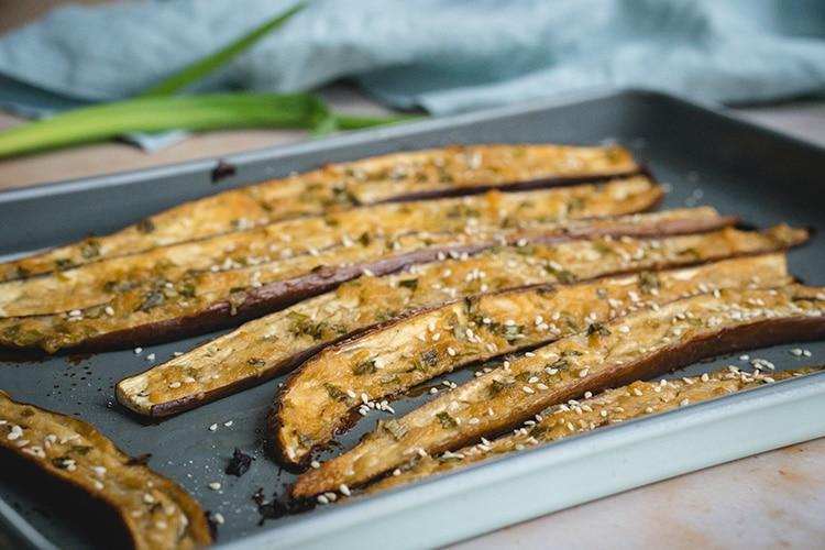Nasu Dengaku sprinkled with sesame seeds on a baking sheet