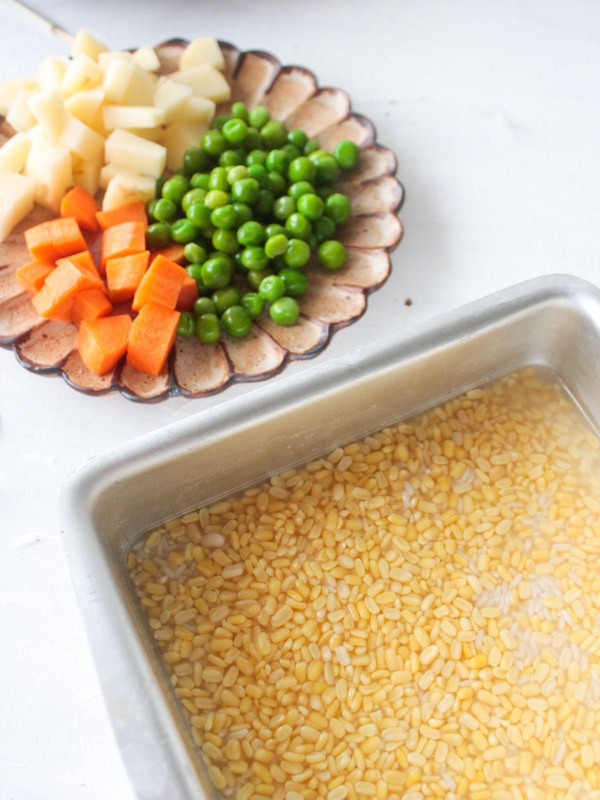 Ingredients for the khichdi  with rice and lentils in metal pan and vegetables on brown bowl