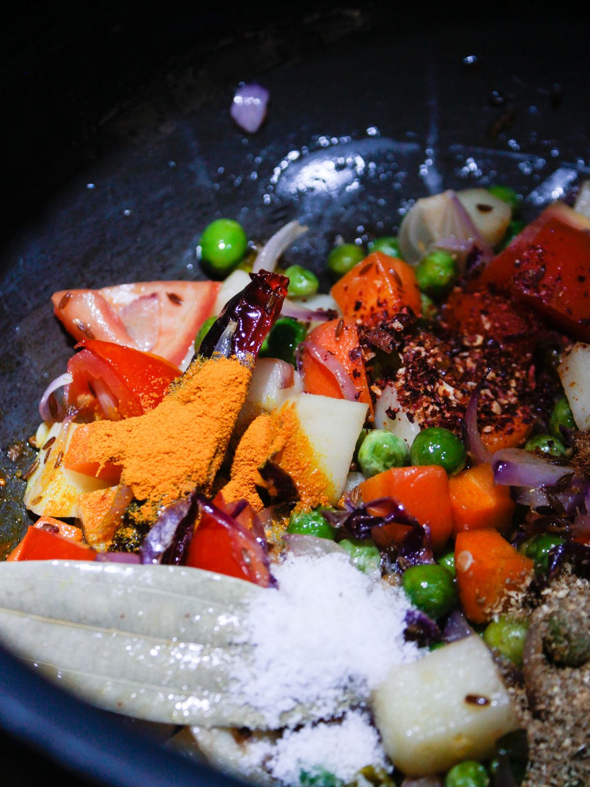 Skillet with tomatoes carrots potatoes peas and dry spices