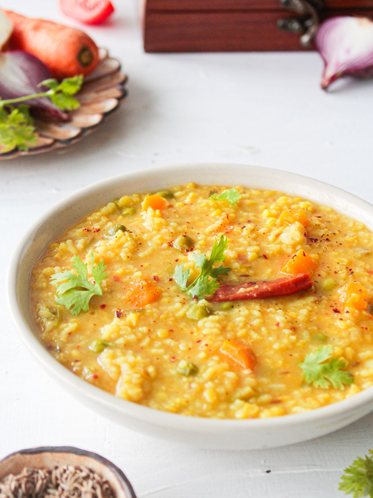 White bowl of rice and lentil porridge on white table by bowl of carrots and shallots