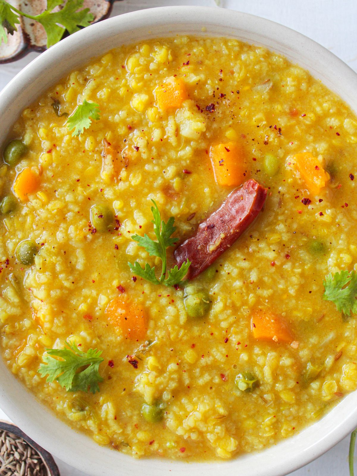 White bowl of khichdi topped with red chili and cilantro