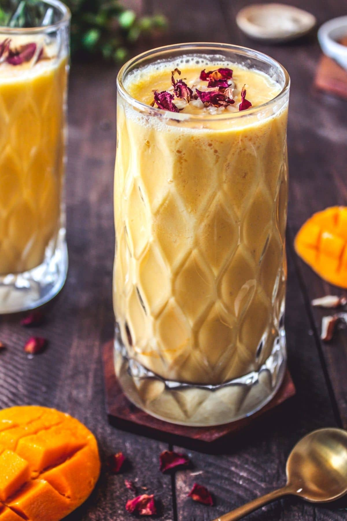 Beveled glasses of mango lassi with rose petals on top