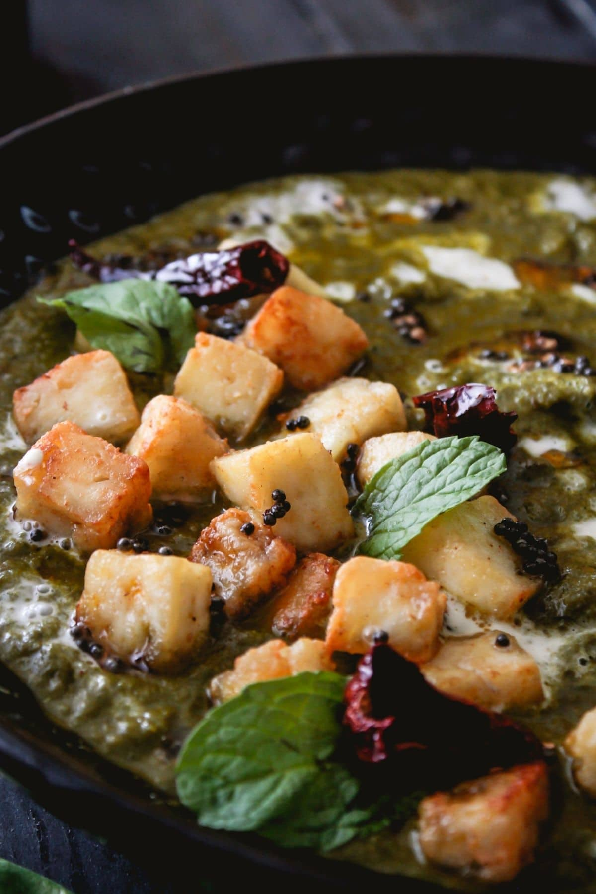 Paneer cubes and red chilies on top of black bowl of palak paneer