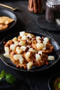Adding chickpeas on top of papdi chaat