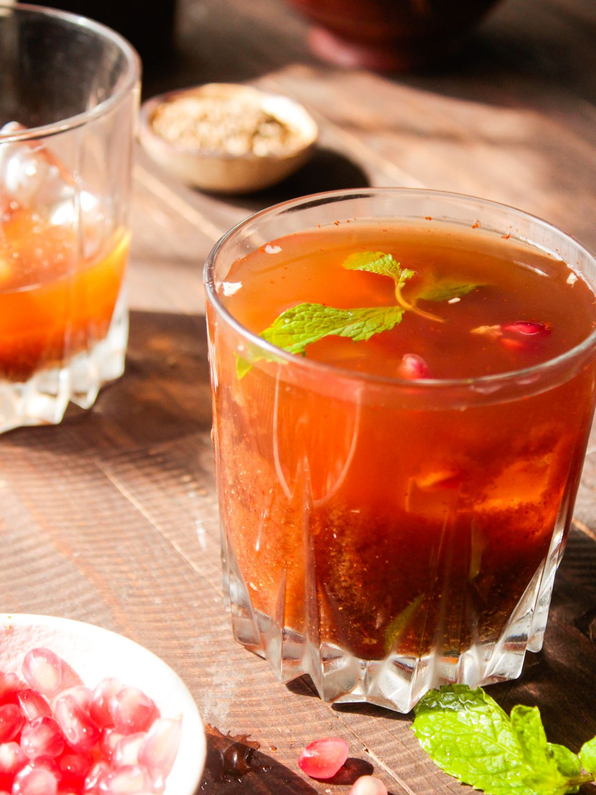 Glass with tamarind cooler topped with mint leaves sitting on wooden table