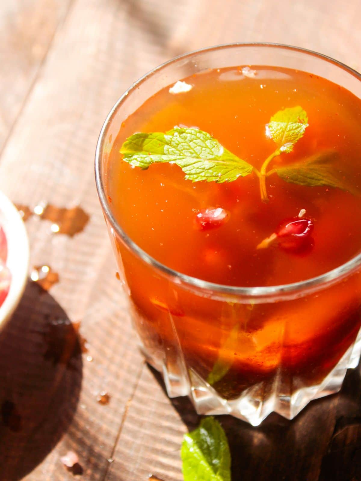 Short glass with red tamarind cooler topped with mint sprig and pomegranate seeds