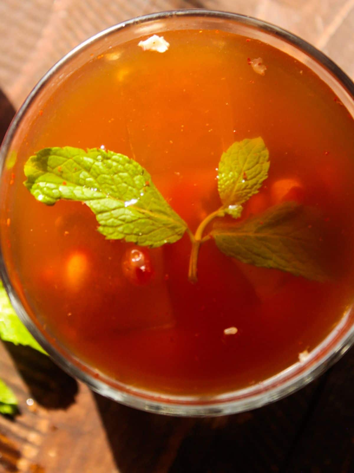 Image looking down at the top of a glass with an orange red drink topped with mint leaves