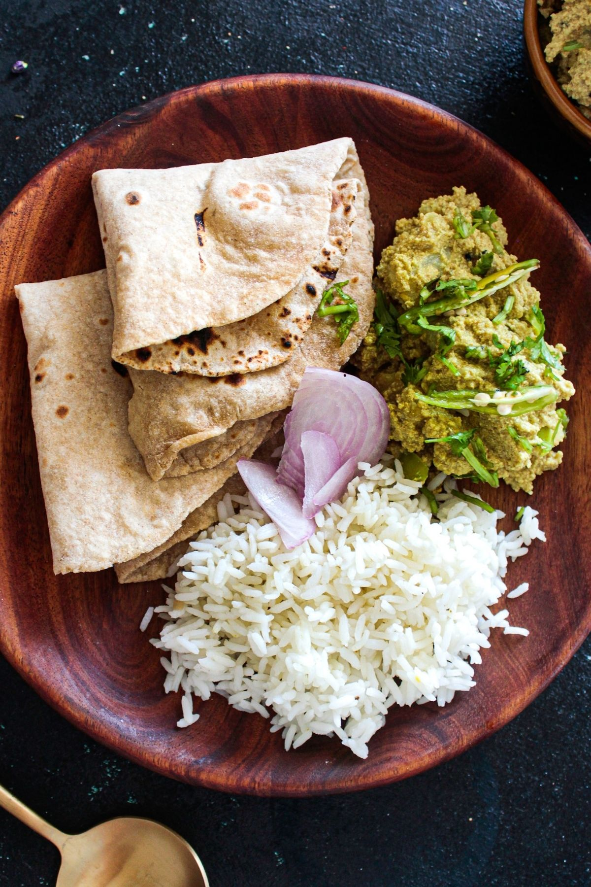 Overhead image of brown plate with rice onion roti and green curry
