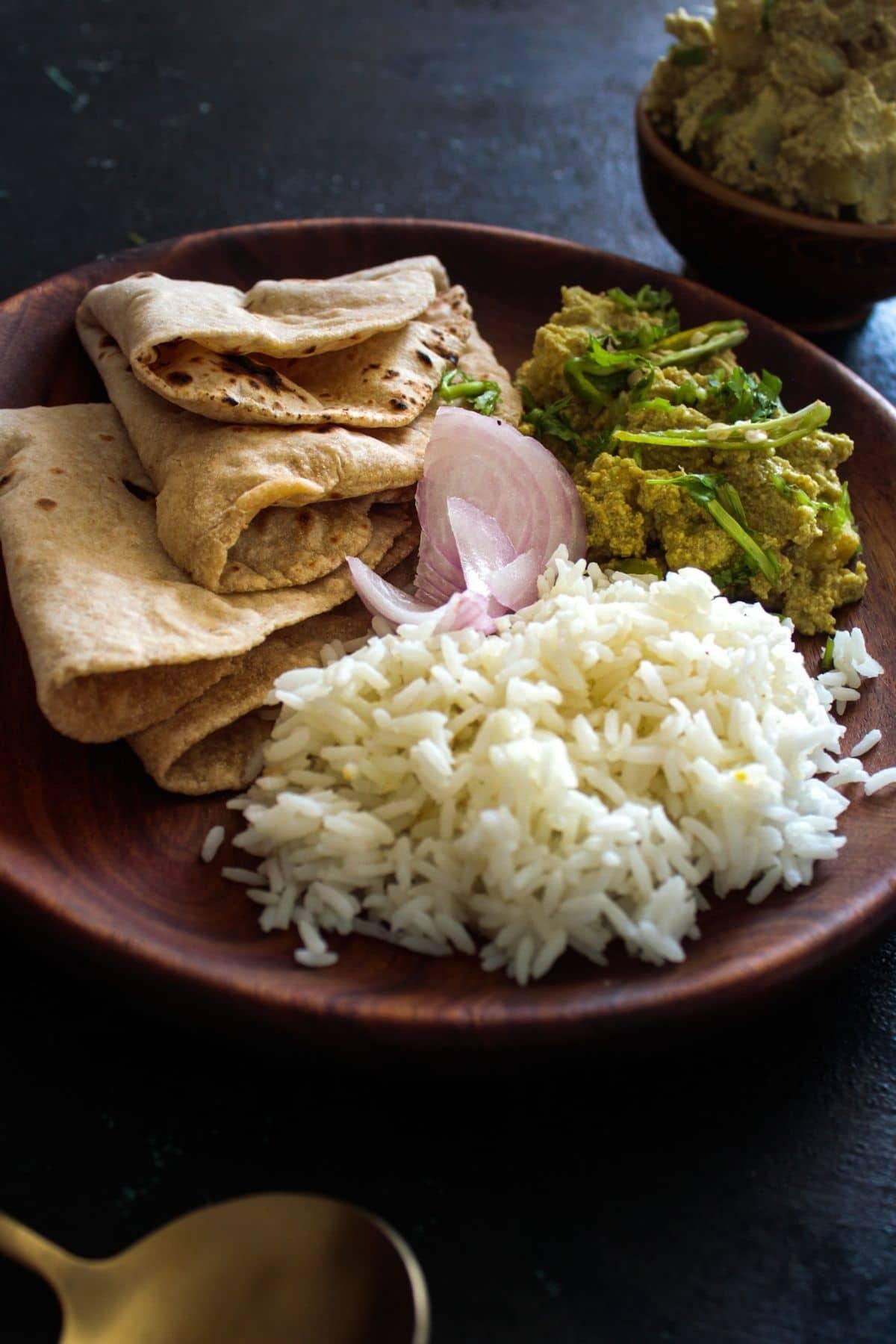 Roti rice and aloo posto on large brown plate on black table