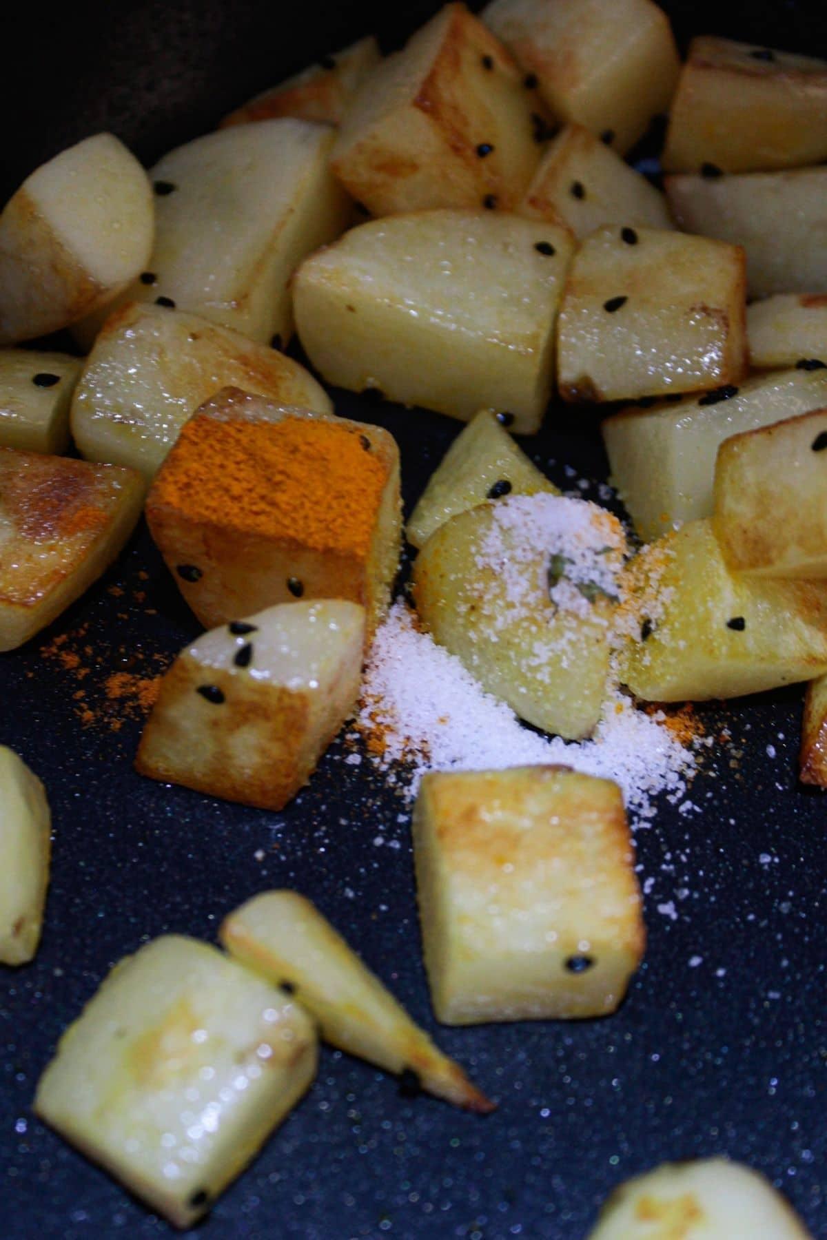Potato chunks in skillet with turmeric and salt