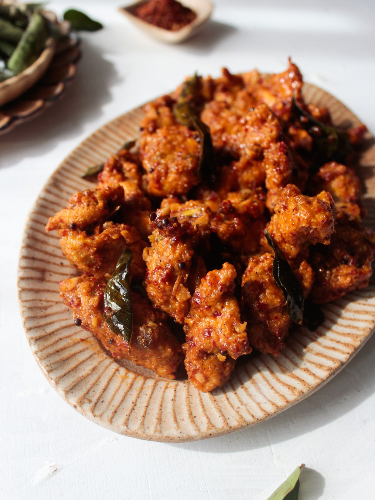Large platter topped with crispy chicken 65 and fried curry leaves sitting on white table