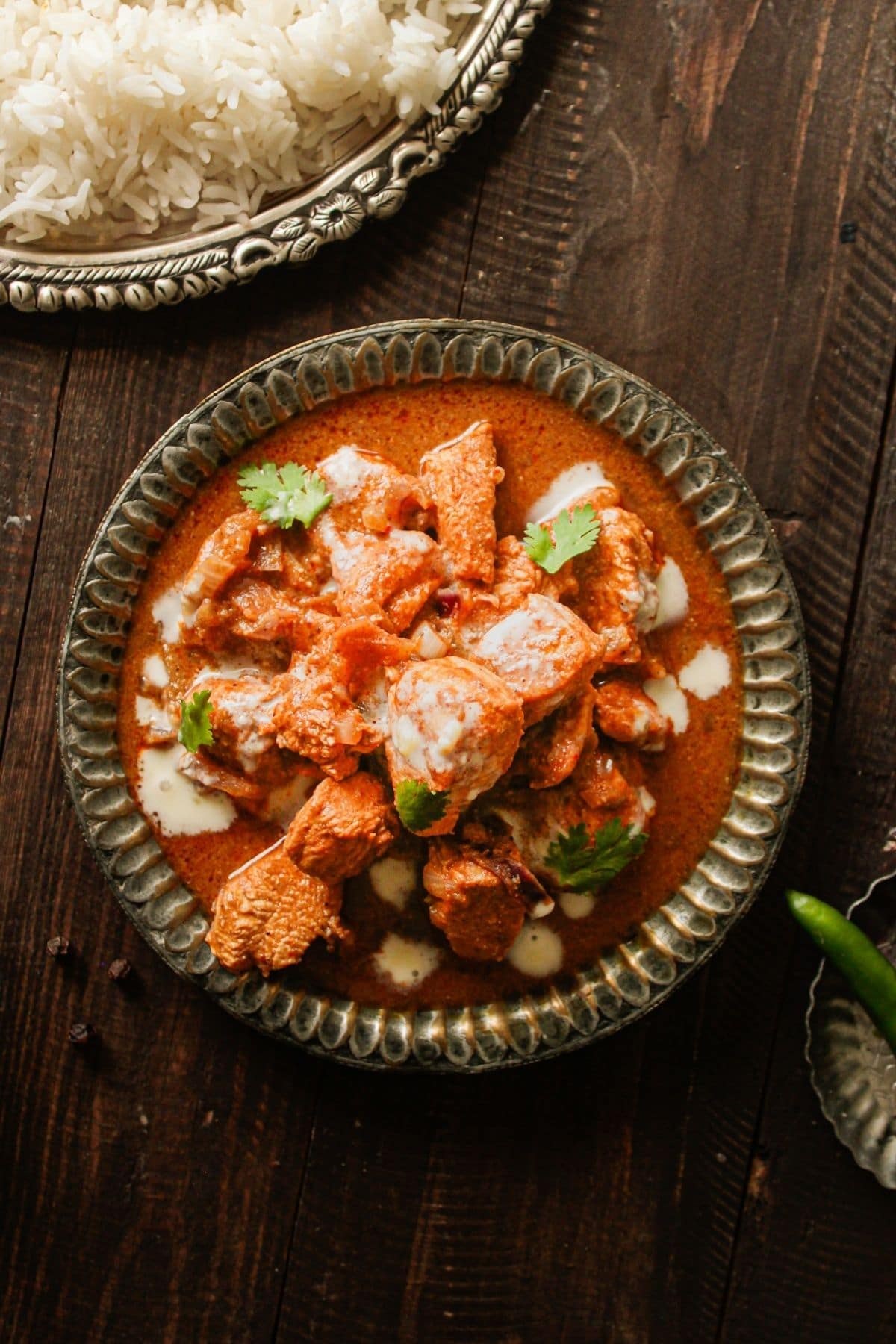 Image taken from above green bowl of chicken vindaloo next to bowl of steamed white rice