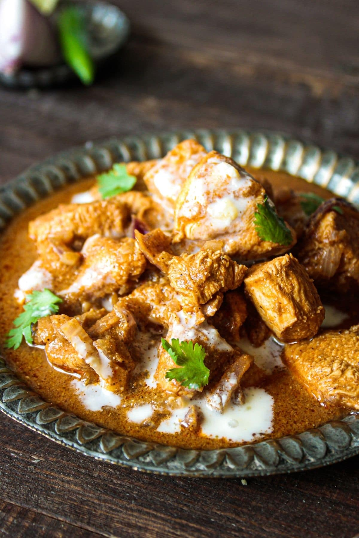 Green bowl of chicken in vindaloo sauce with cilantro and cream on top
