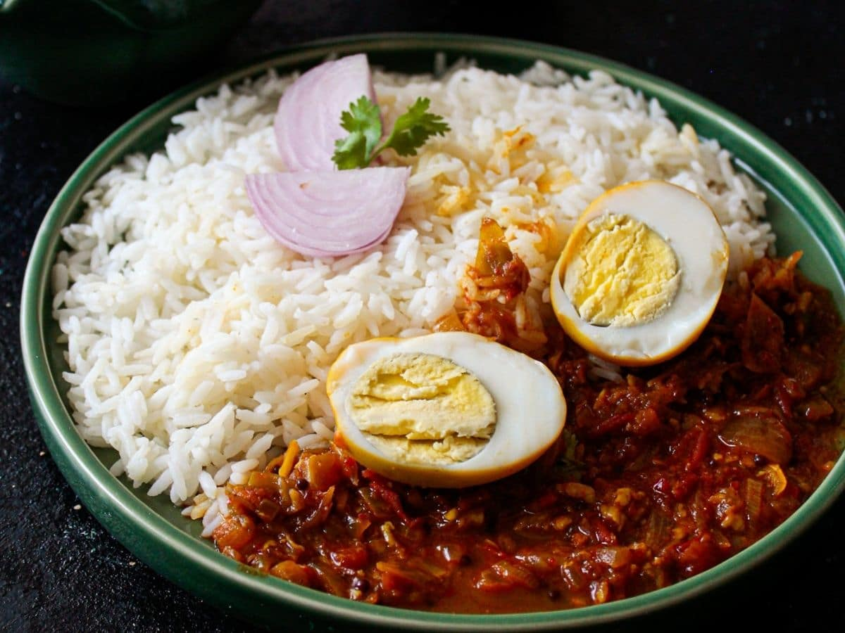 Green bowl of curry with rice red curry and sliced eggs on top
