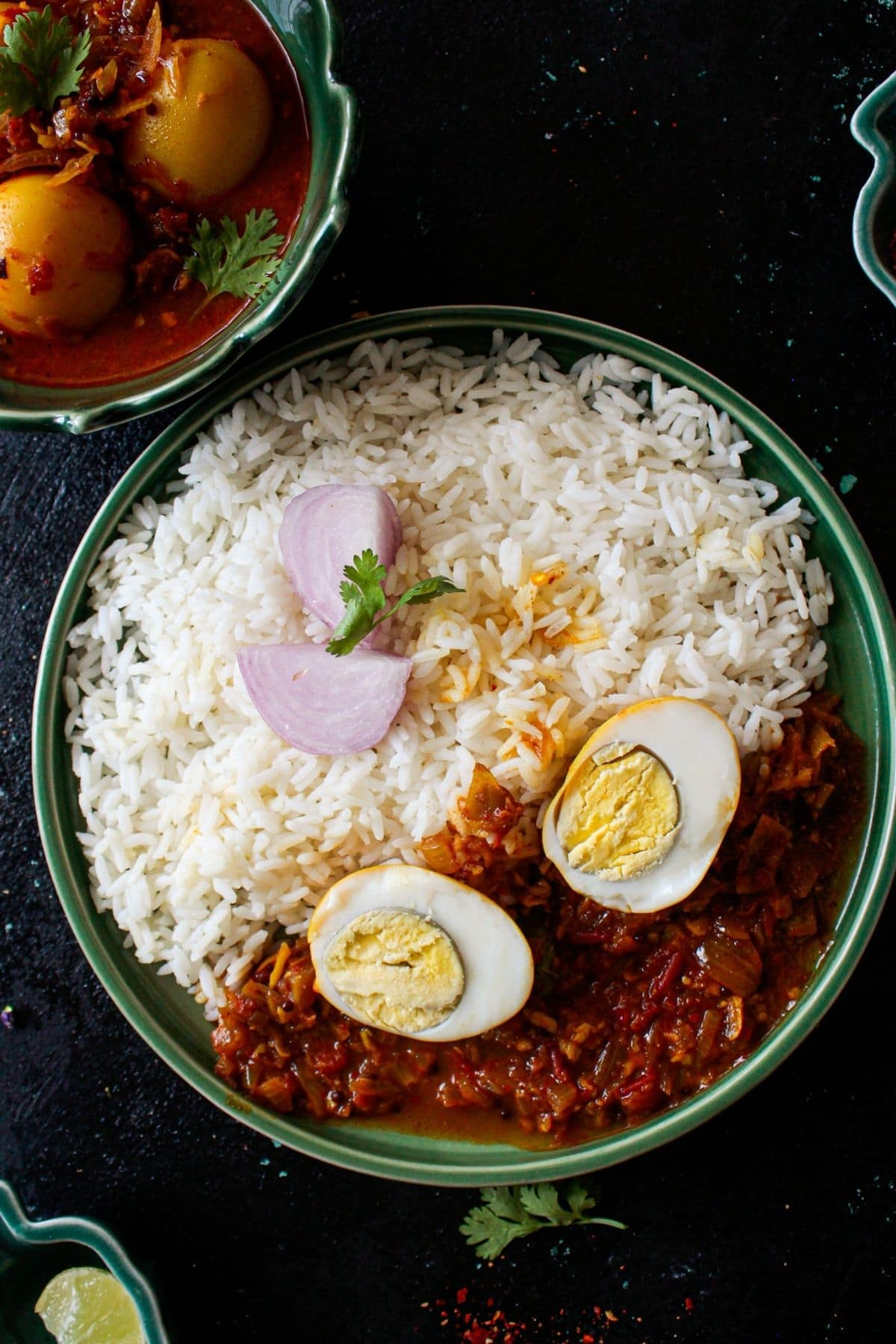 Green bowl with rice and curry next to boil of curry with whole eggs