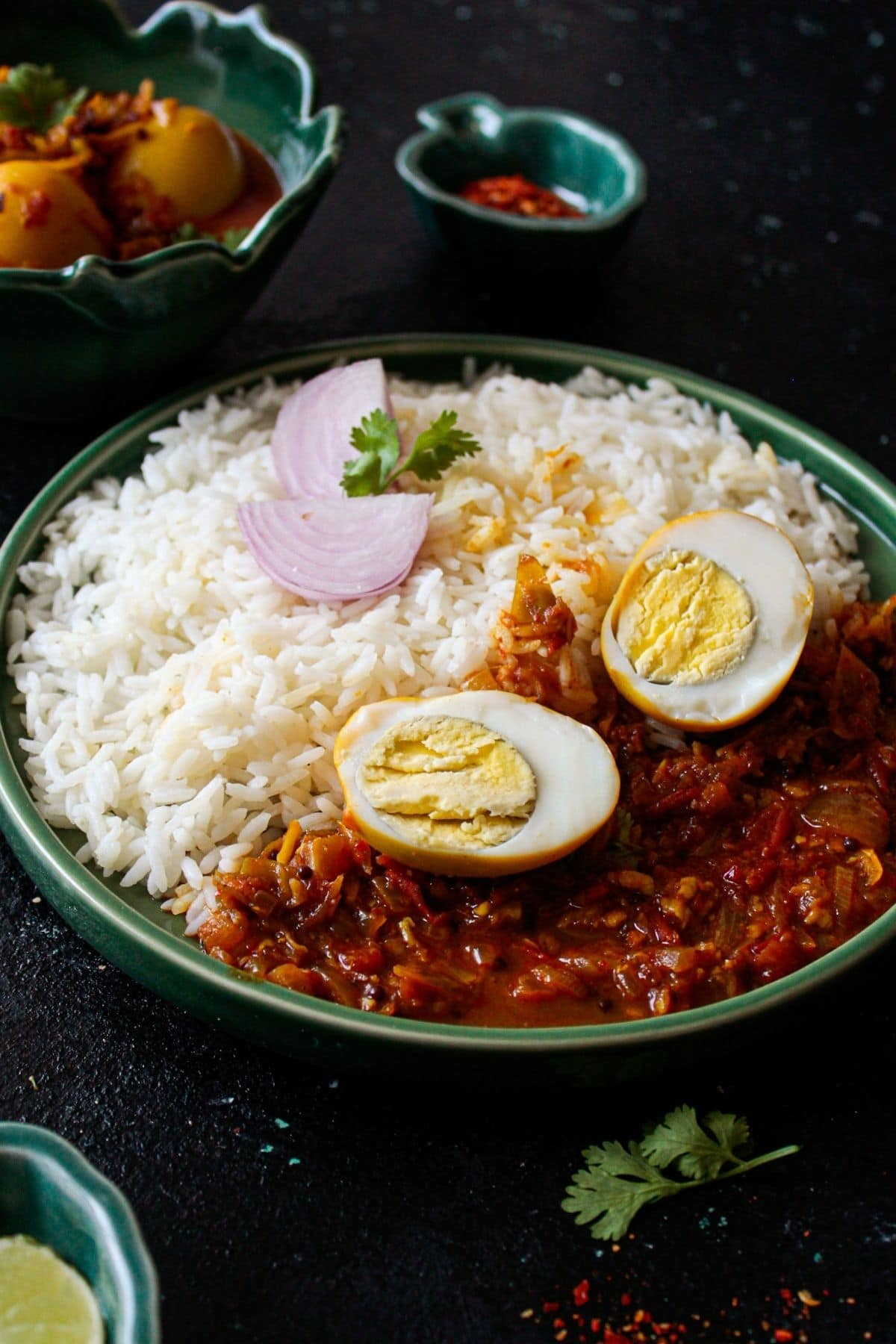 Sliced hard boiled egg on top of red curry by rice in green bowl