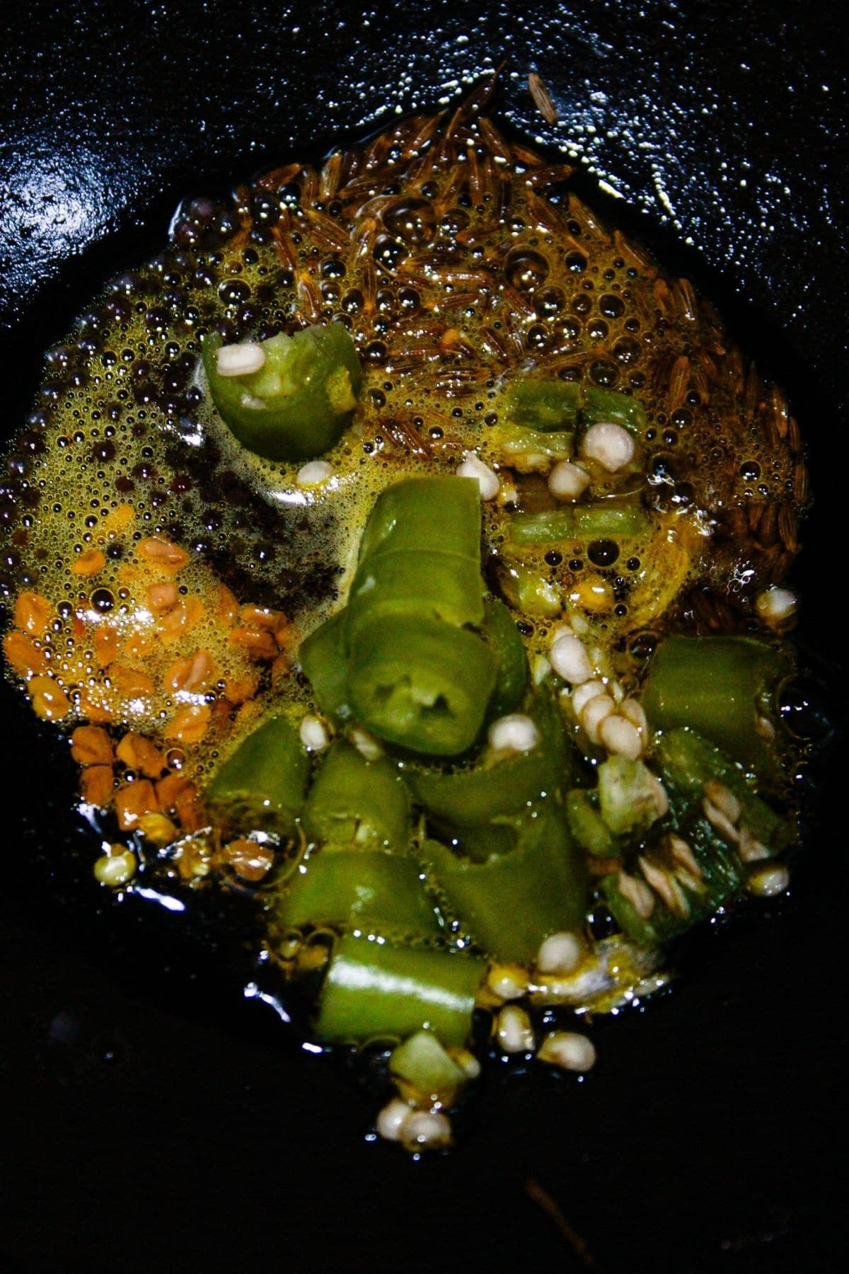 Oil seeds and chiles in skillet