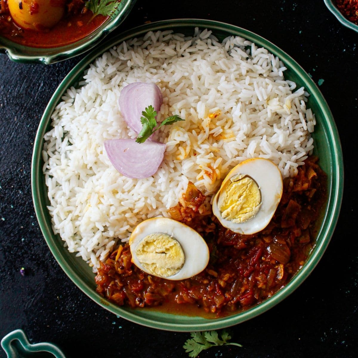 Bright green bowl filled with rice and egg curry with egg cut in half