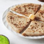 Sliced aloo paratha on white plate