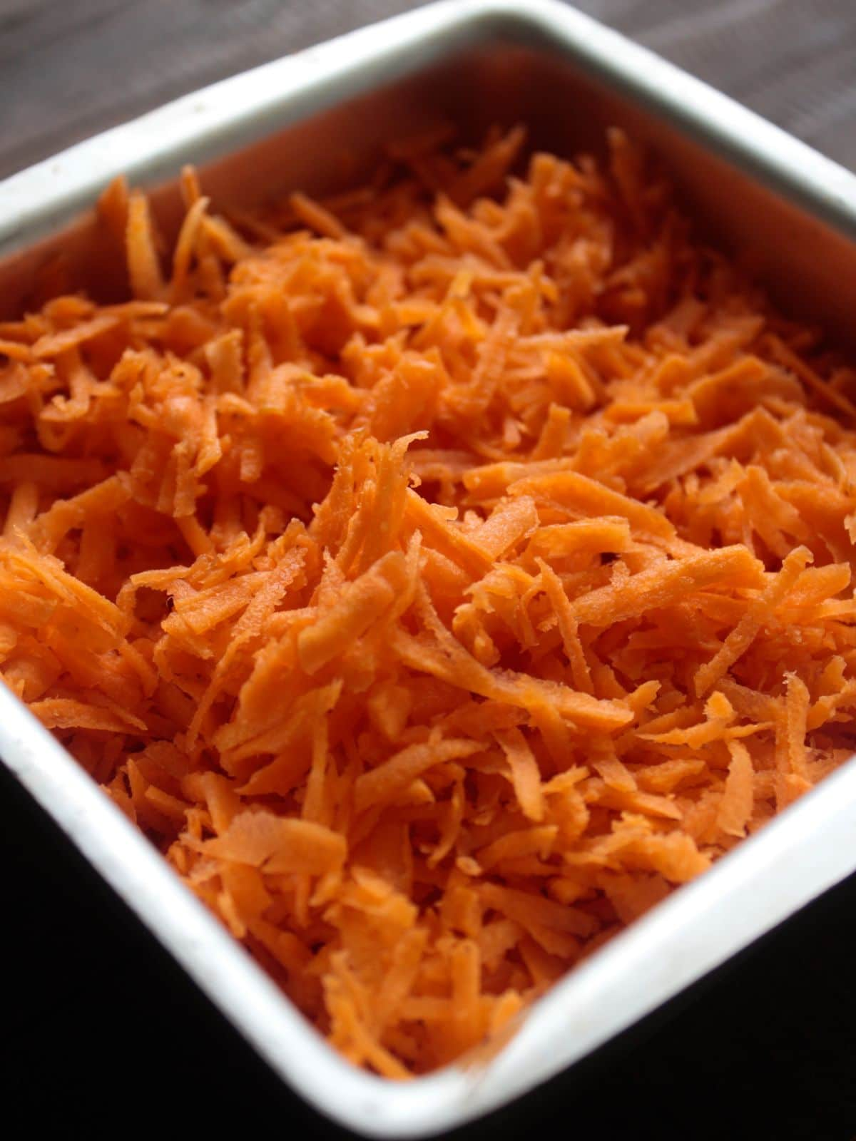 Large square white bowl filled with shredded carrots