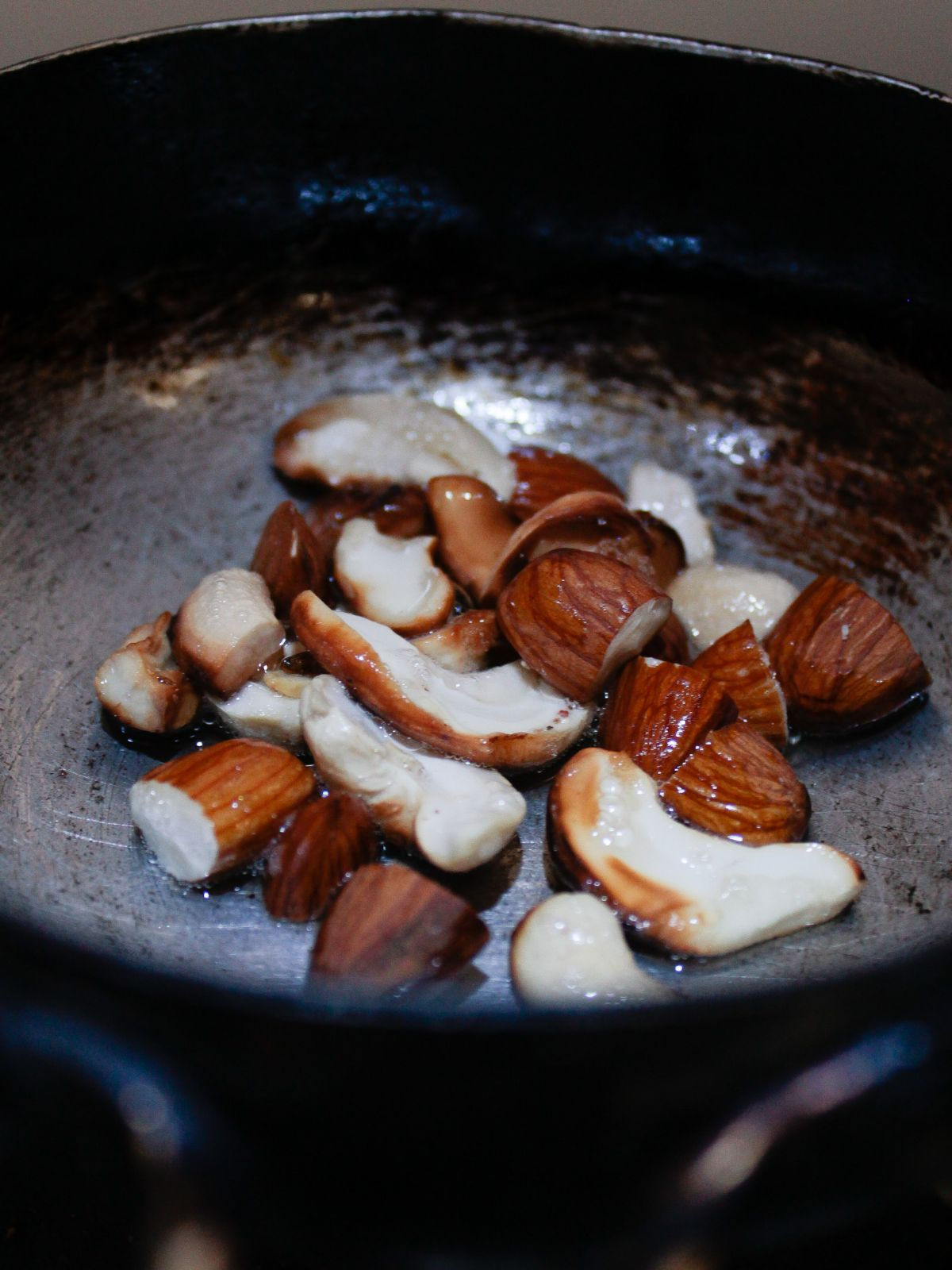 Large skillet over fire with cashews and almonds roasting