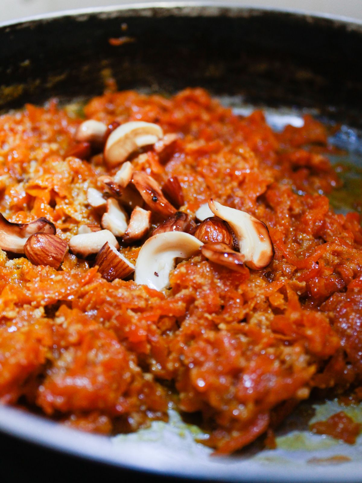 Gajar ka Hawla in large skillet topped with cashews and almonds