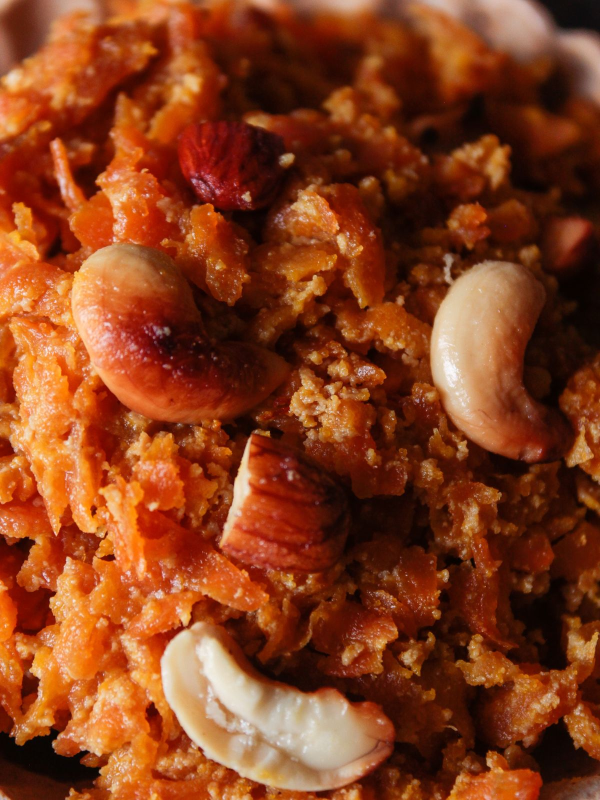 Close picture of shredded carrots topped with almond and cashew pieces