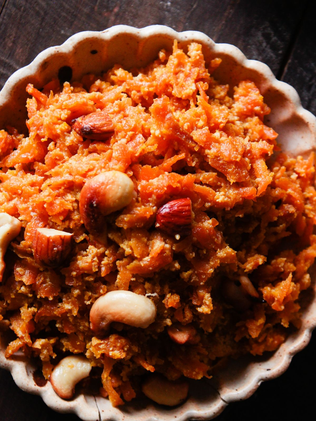 finished carrot halwa in large cream bowl with scalloped edges