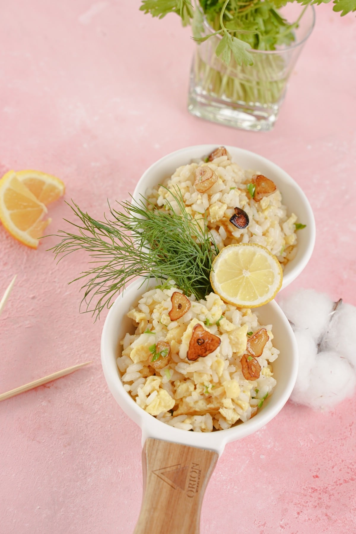 Rice in white bowls topped with herbs and lemon slice