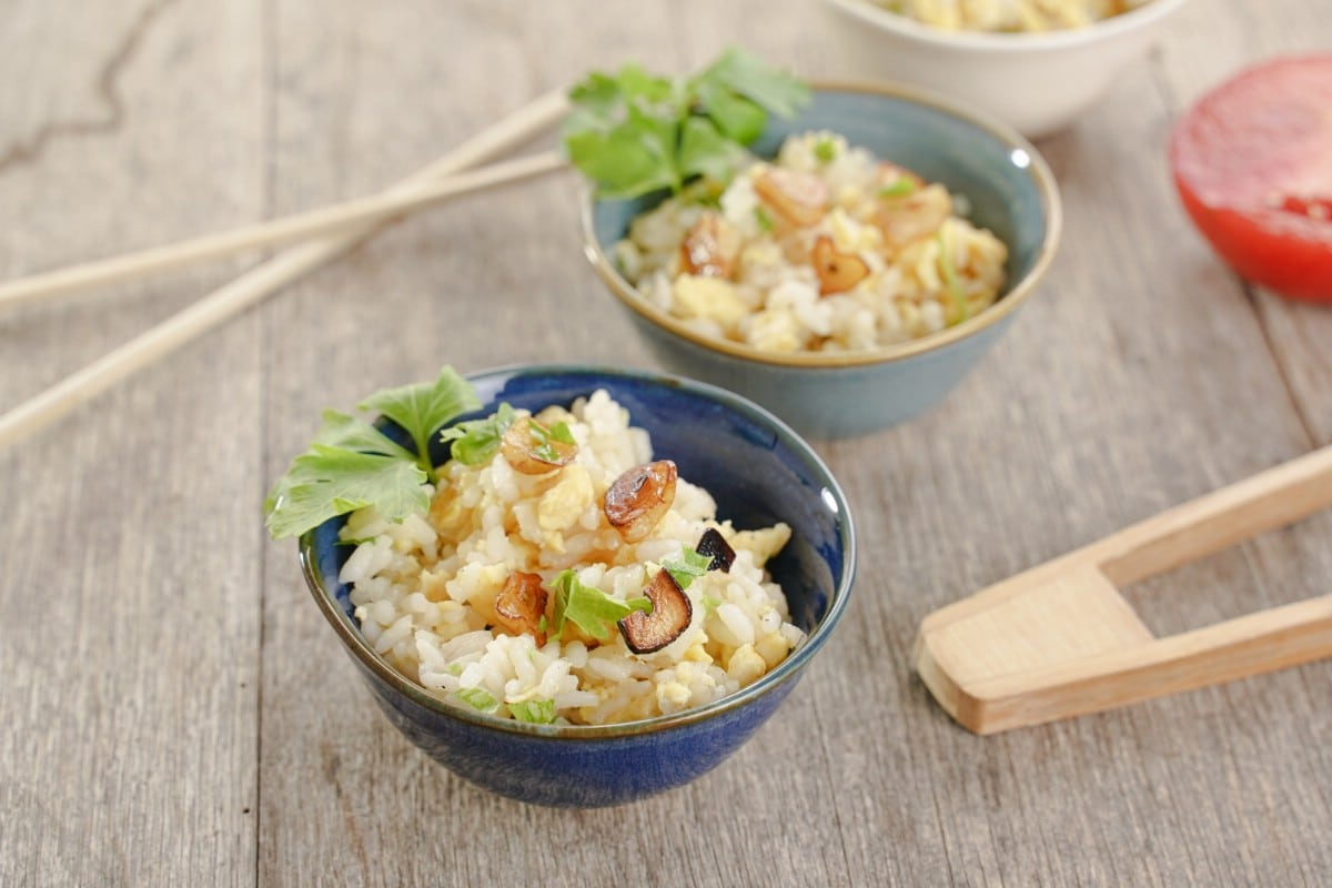 Small blue bowl of garlic fried rice next to chopsticks on brown table