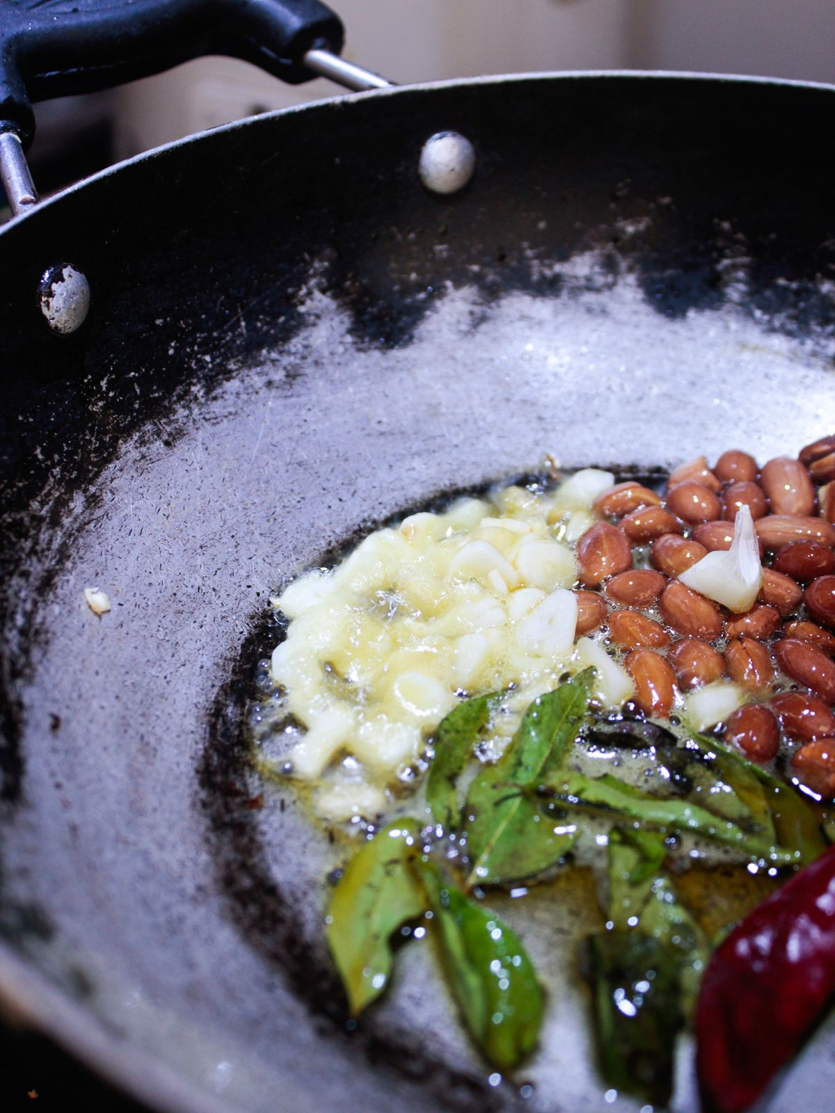Skillet with oil curry leaves peanuts and hing cooking