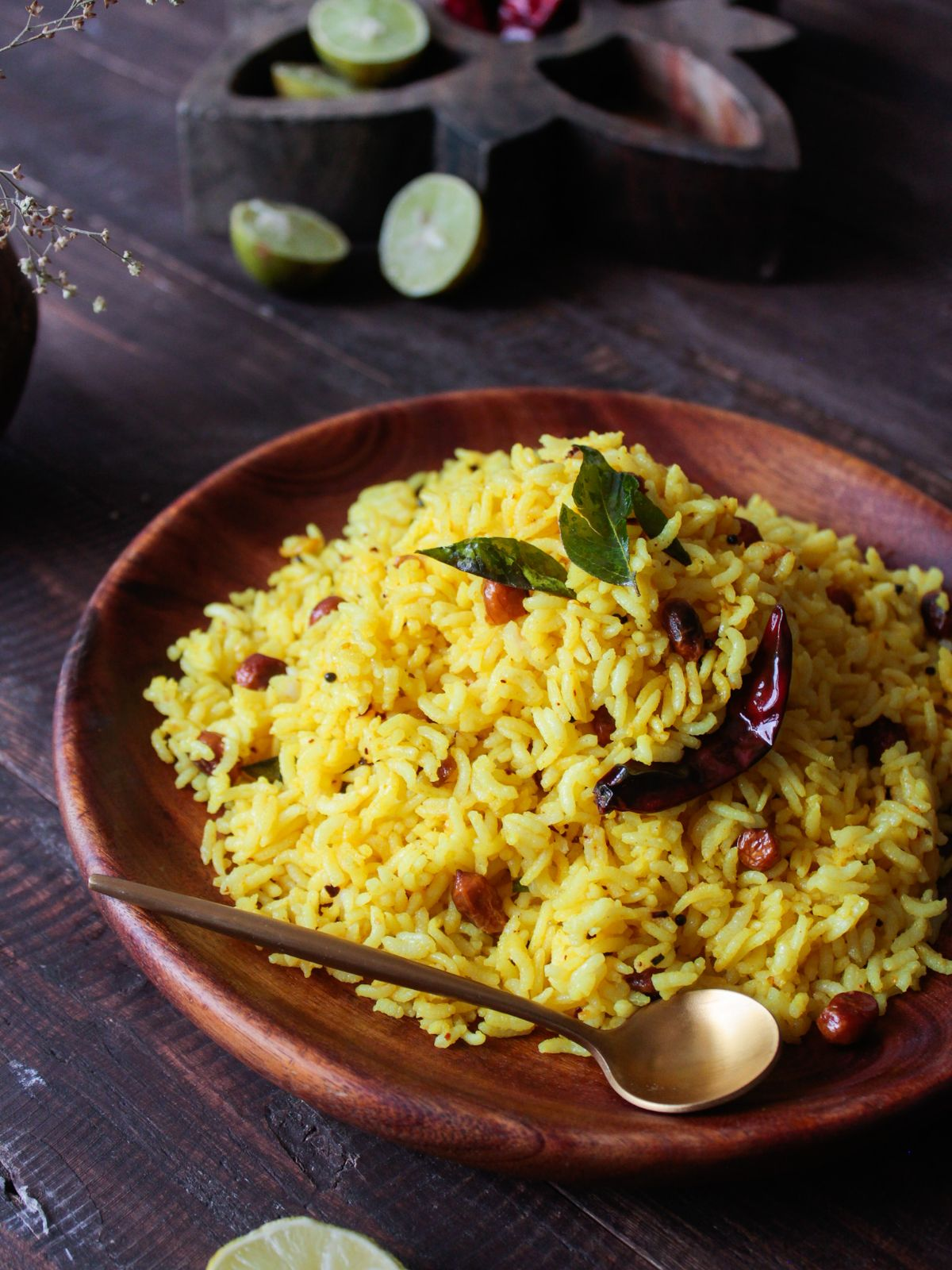 Lemon rice in wooden bowl with gold spoon on wood table