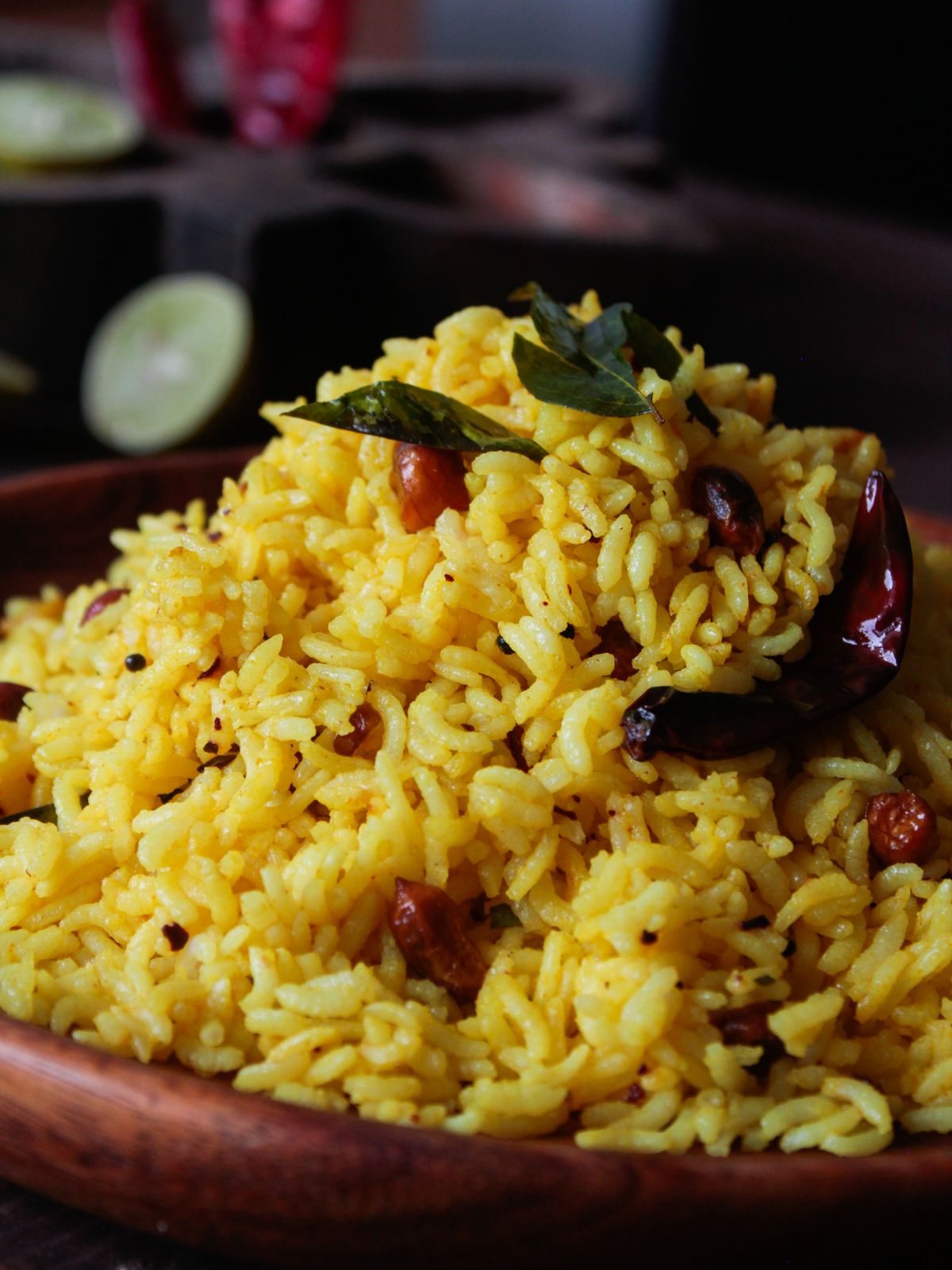 Wooden bowl of yellow rice with peanuts and coriander leaves on top