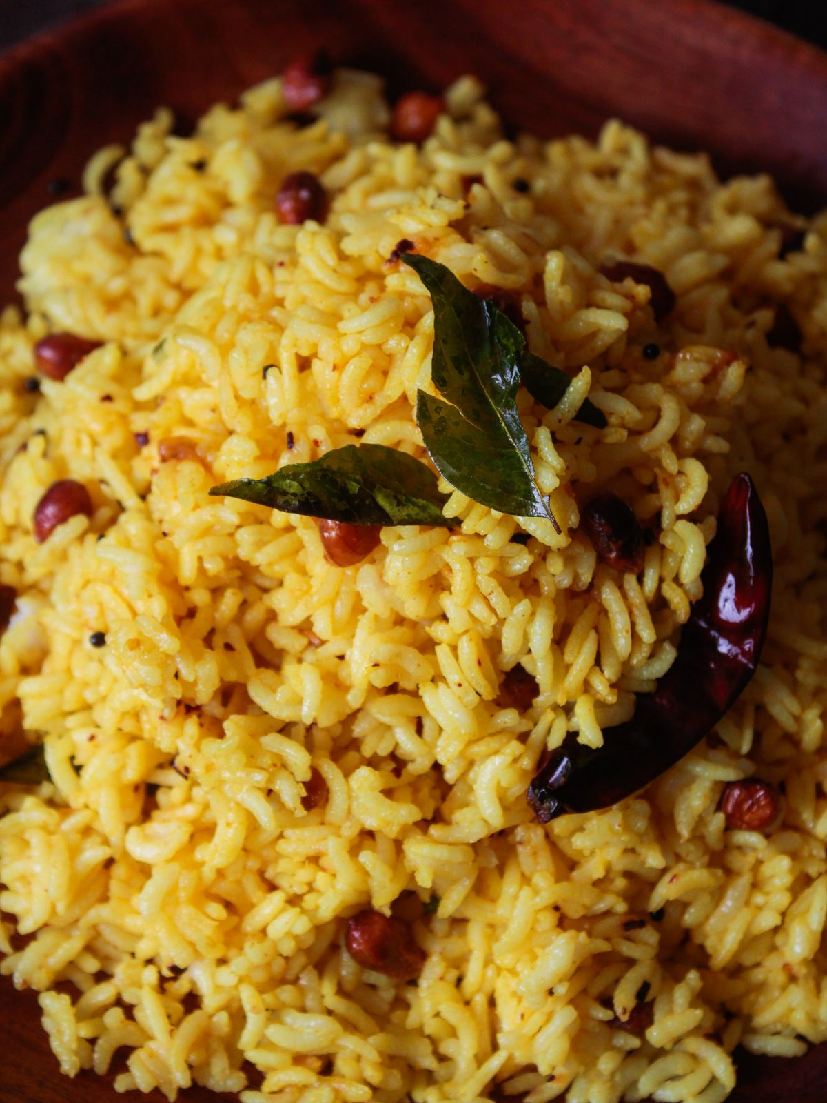 Close up image of bowl of yellow rice with curry leaves red chile and peanuts mixed in