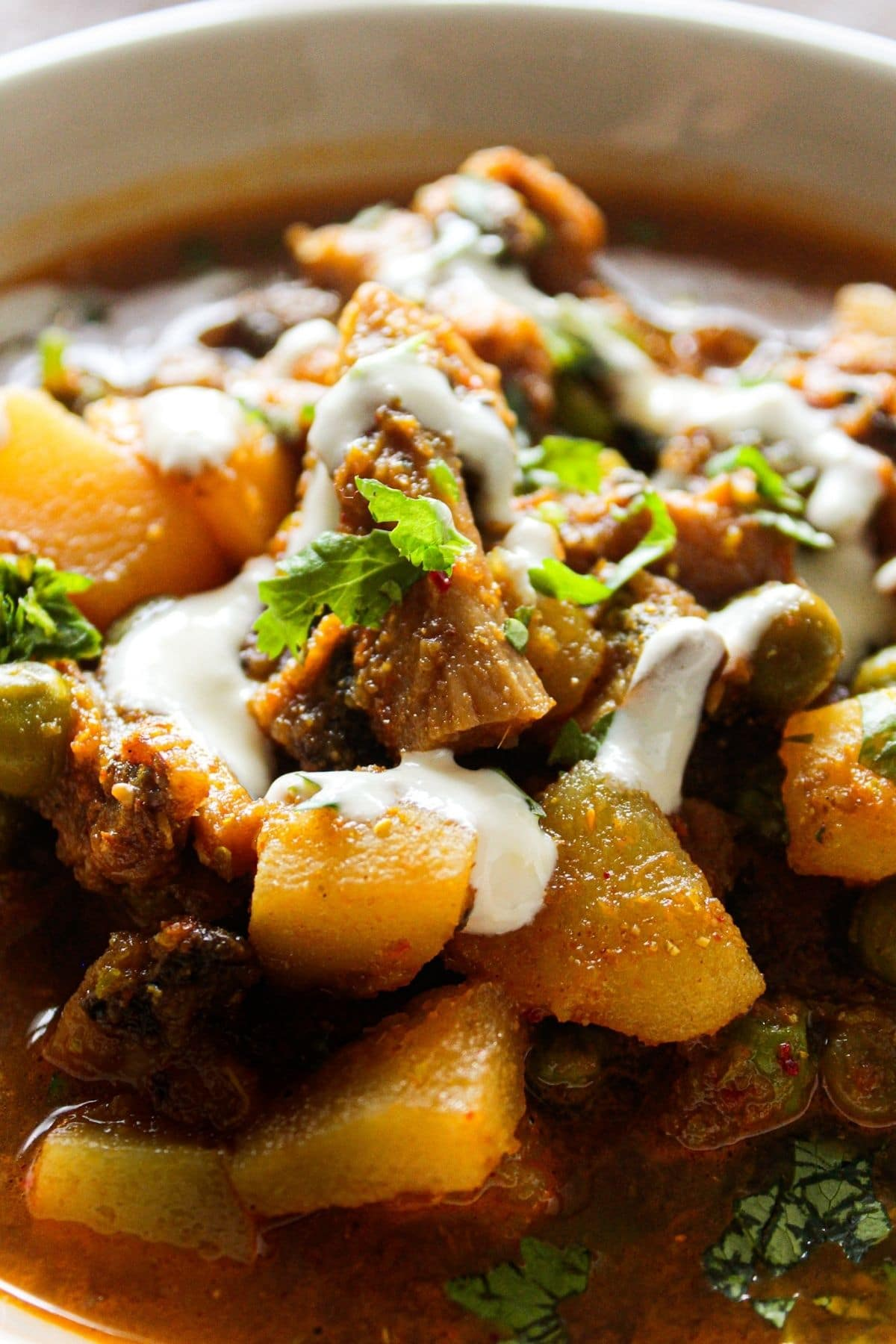 Close up image of mushroom and potato curry topped with cream and cilantro
