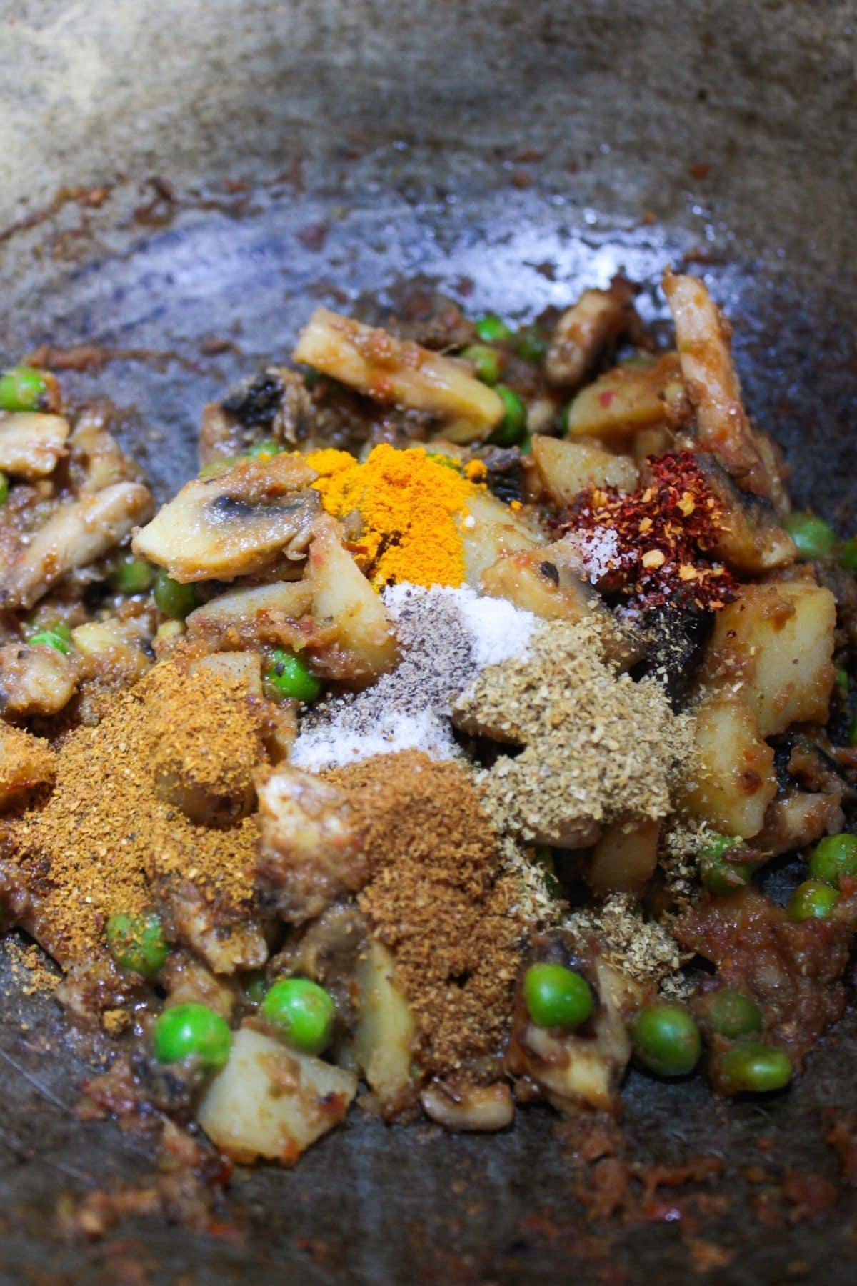 Seasonings on top of vegetables in skillet