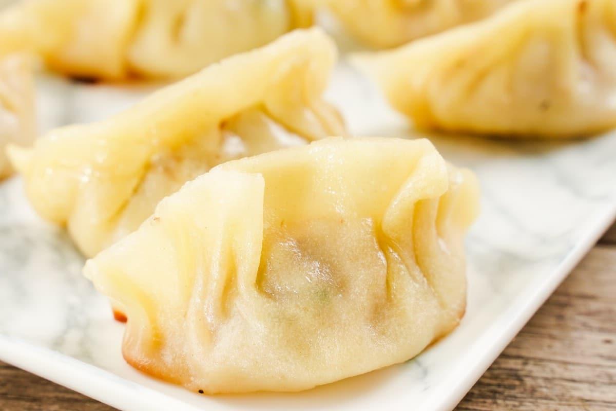 Close image of white plate of dumplings